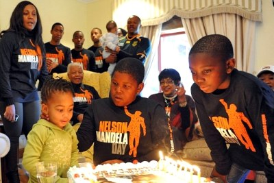 Nelson Mandela watches with other family as great-granddaughter Zamakhosi Obiri & grandson Mbuso Mandela look at his cake in Qunu, South Africa on his 93rd birthday.