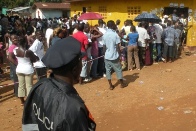 A police officer monitors a voting queue.