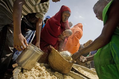 Women and children wait to receive a cooked meal at a food distribution organized by the WFP near the port in Mogadishu, Somalia