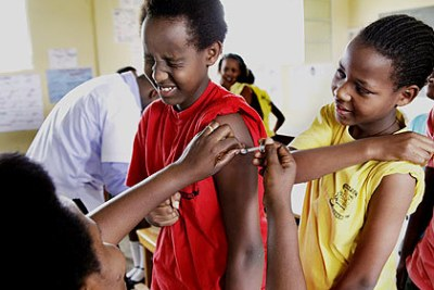 Seraphine Mukanyarwaya, Nurse at Kagugu Health Centre Immunizing pupils of Apapec Irebero Primary School.