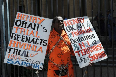 Prison rights activist Golden Miles Bhudu demonstrates outside the Johannesburg High Court, where Nigerian Henry Okah, found guilty of masterminding two car bomb blasts in Abuja, appeared for pre-sentencing proceedings.
