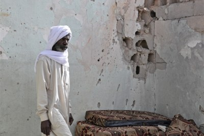 A resident of Tayuri stands against a bullet-riddled wall of his house.