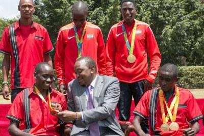 President Uhuru Kenyatta admires Paralympic athlete Henry Kirwa's medal during a ceremony at State House.