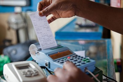 A trader pulls out a sales receipt from an electronic billing machine.
