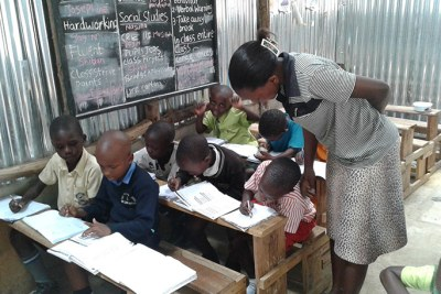 A teacher attends to learners at Bridge International Academy Katooke.