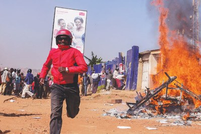 A boda-boda rider flees from the burning Boda Boda 2010 offices in Nateete on Monday.