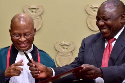 President Cyril Ramaphosa hands a pen to Chief Justice Mogoeng Mogoeng after being sworn in at a ceremony in Cape Town Thursday.