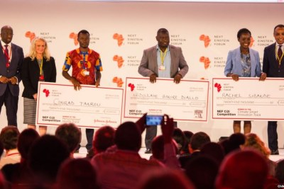 Dr. Conrad Tankou, Rachel Sibande and Dr. Abdoulaye Diallo stand on the stage at NEF holding the U.S.$25,000 checks that they won for their innovation prizes.