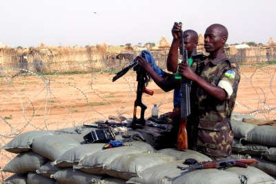 AU soldiers cleaning their guns in their Tawilla base, adjacent to Rwanda IDP camp, North Darfur.