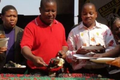 le président des jeunes de l'ANC, Julius Malema partage un gateau avec des étudiants