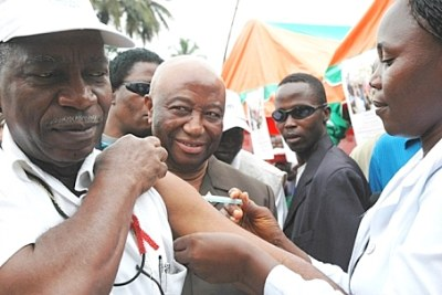 Liberian Health Minister Dr Walter Gwenigale receives a yellow fever vaccination.
