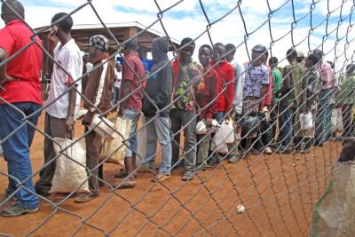 File photo of refugees at Dzaleka camp in Malawi waiting in line to collect their monthly food rations which were cut by half in March 2012 due to a funding shortfall