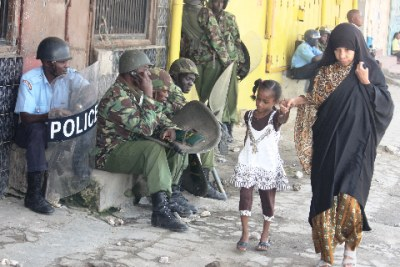 A woman and child pass by a squad of riot police at Majengo in Mombasa (file photo).
