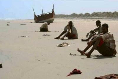 Des survivants exténués par la traversée du golfe d'Aden attendent des secours sur une plage au Yémen