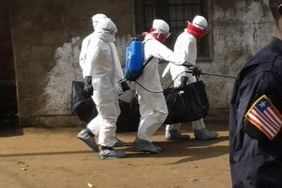 A burial team carries the body of a suspected Ebola victim from a community in Monrovia under the watchful eyes of police officers.