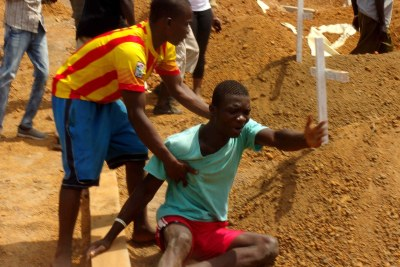 The brother of the victim of an earlier Ebola outbreak in West Africa breaks down at his graveside.