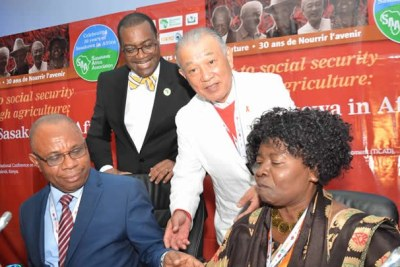 Chiji Ojukwu, AfDB Director of Agriculture and Agro-industry, and Ruth Oniang'o, Chairperson of the Sasakawa Africa Association, sign an MOU to promote agriculture and agri-business in Africa. Witnessing the ceremony are AfDB President Akinwumi Adesina (standing left) and Yohei Sasakawa (right).
