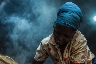 Catherine Wambu uses her M-KOPA solar powered light to cook at night.