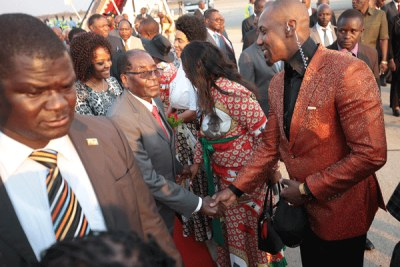 President Robert Mugabe greets his son-in-law, Simba Chikore at Harare International Airport (file photo).