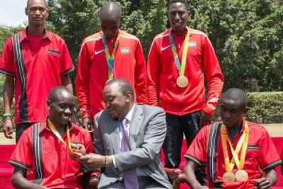 President Uhuru Kenyatta admires Paralympic athlete Henry Kirwa's medal during a ceremony at State House.