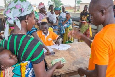 Une mère et un nourrisson recevant le premier paiement de virement en espèces dans le cadre du programme LEAP 1000 du gouvernement ghanéen dans le village de Wantugu, région du Nord du Ghana.