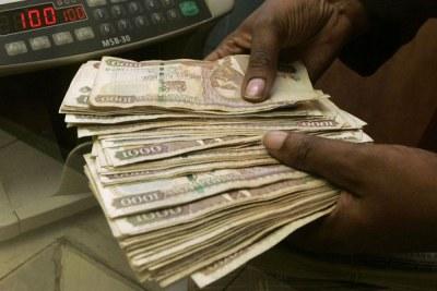 A teller counts money at a Kenyan bank (file photo).