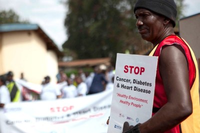 Mike of the Uganda NCD Alliance leads a parade around the community in Kampala to raise awareness of NCDs.