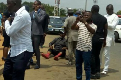 Senator Dino Melaye, sitting on the floor after jumping out of a moving police van.