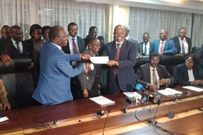 University Academic Staff Union Secretary-General Constantine Wasonga and Inter Public Universities Councils Consultative Forum Chairman Paul Kanyari exchange documents after signing a return to work formula.
