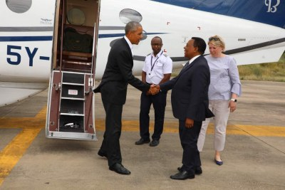 Former US President Barack Obama shakes hands with Tanzania Foreign Minister Augustine Mahiga at the Kilimanjaro International Airport on Sunday, July 15, 2018.