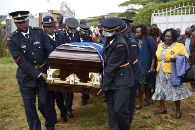 Police carry a casket bearing the remains of the late Nicholas Bett, former World 400m hurdles champion, on arrival at their home in Simat, Uasin Gishu County, as Bett's wife Gladys Bett second (right) and mother Esther Boit follow on August 15, 2018.