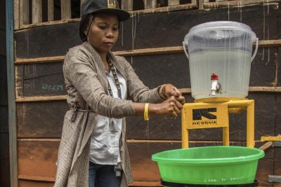 Dr. Sylvie Musema Ngimba washes her hands with chlorine and water at Case Du Salut Medical Center where she is head medical doctor for infection prevention and control at the International Rescue Committee. She has worked to contain five Ebola outbreaks.