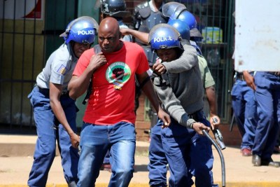 Riot police clash with Zimbabwe Congress of Trade Unions activists in Harare.