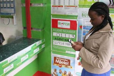 A woman withdraws money from an M-Pesa outlet in Nyeri (file photo).