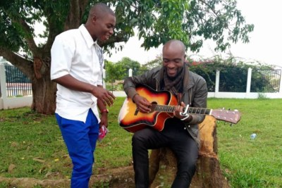 From left, Emmanuel Bilashi and Lindfort Ci sing in Bamenda, Cameroon.
