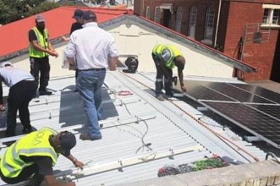 Une équipe installe des panneaux solaires sur le toit d'un des bâtiments de l'école secondaire de Salt River