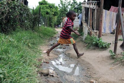 Children jump over a stream of sewage flowing in Chitungwiza.