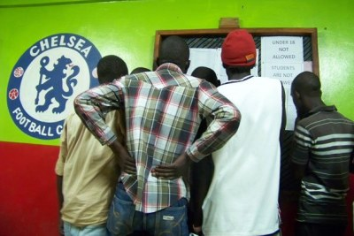 Youth look at football fixtures at a sports betting centre in Arua District recently. Several students in Nebbi District have resorted to sports betting.