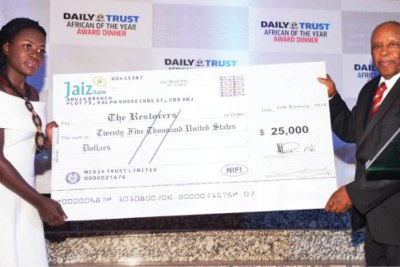 Former Botswanan president Festus Mogae (right) presents the $25,000 prize to Stacy Owino, the team leader of the Kenyan schoolgirls who won the Daily Trust African of the Year award (2018).