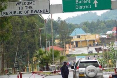 Contrôle à la frontière. Un agent de sécurité rwandais inspecte un véhicule du côté ougandais au poste frontière de Cyanika.