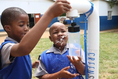 Children fill up their bottles of water from a GreenSource tap in South Africa on 22 April 2019.