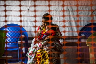 A mother holds her child in the zone where people suspected of being infected by Ebola are held in quarantine at the Ebola Transition Center in Beni, North Kivu, January 18, 2019.