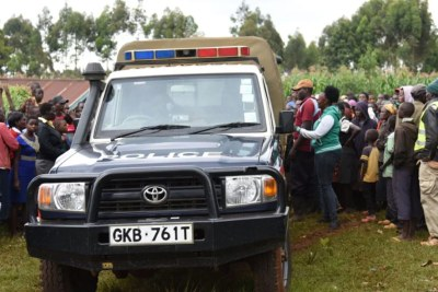 Members of the public mill around a police vehicle carrying the body of a man who was found dead in a maize farm in Sachangwan-Chebyakwai, near Eldoret International Airport in Uasin Gishu County.