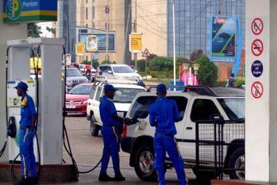 Un pompiste remplit le réservoir de carburant d'une voiture.
