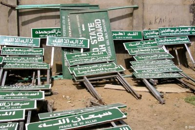Signs in northern Nigeria exhorting people to live their lives according to Islamic Sharia principles.
