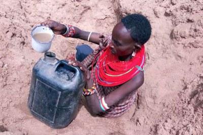 A woman fetches water from sandy holes in Ntepes, Samburu County in Kenya (file photo).