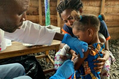 Un professionnel de santé vaccine une fillette contre la rougeole en République démocratique du Congo.