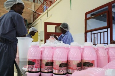 Workers on a yogurt packaging line at a dairy firm that still uses single-use plastics at Special Economic Zone in Kigali.