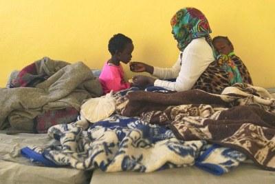 Une mère détenue, avec son bébé endormi sur le dos, donne du pain à son autre enfant dans la salle réservée aux femmes d'un centre de détention à Benghazi, en Libye.