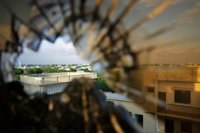 The skyline beyond the northern suburbs of Mogadishu in Somalia, seen through a bullet hole in the window of a hotel.
